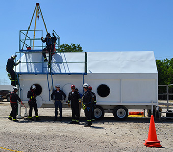 تدريبات الإنقاذ في الأماكن الضيقة. دورة إنقاذ تدريبية عملية بالموقع تُدرس الإجراءات المناسبة للأماكن الضيقة في مواقف الطوارئ.